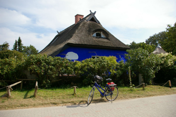 Blaues Fahrrad vor blauem Haus auf Hiddensee